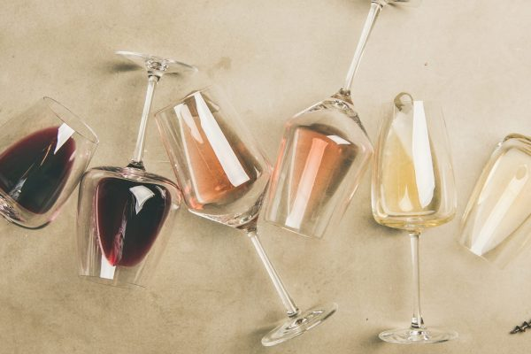Flat-lay of red, rose and white wine in glasses and corkscrews over grey concrete background, top view, wide composition. Wine bar, winery, wine degustation concept